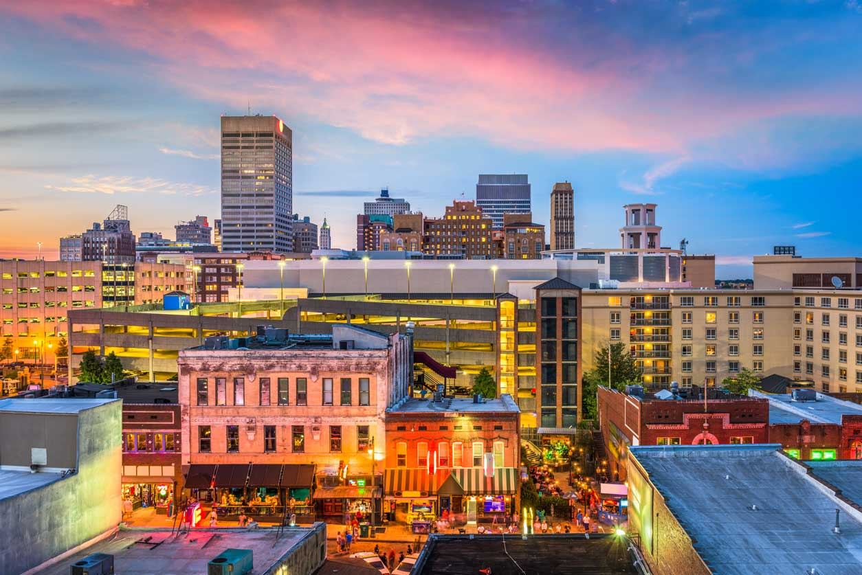Cityscape of dowtown Memphis, Tennessee at sunset. Focus on orange glow of street lights and red/pink hue of sunset and brick buildings