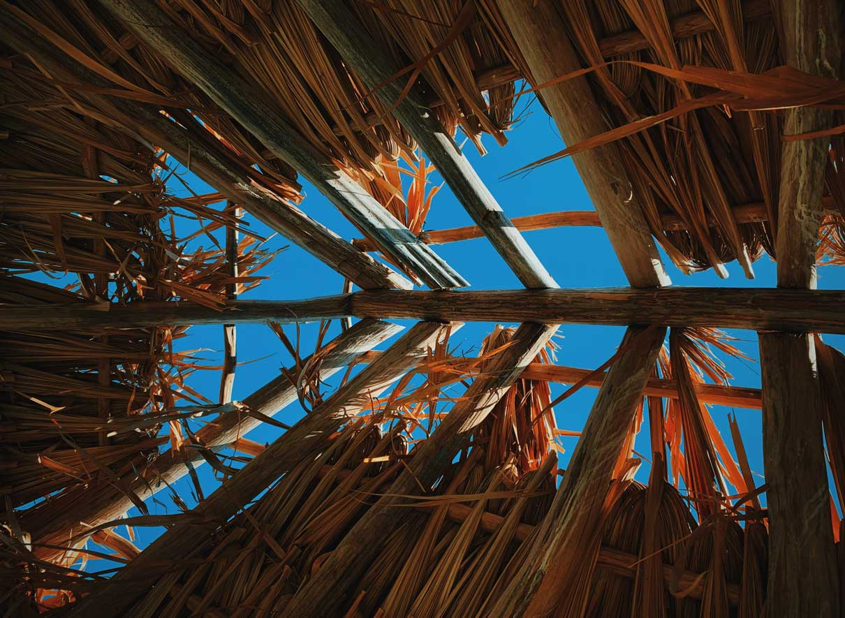 Wooden Roof Structure with sky visible through the beams. Structure is being covered with dried reeds.