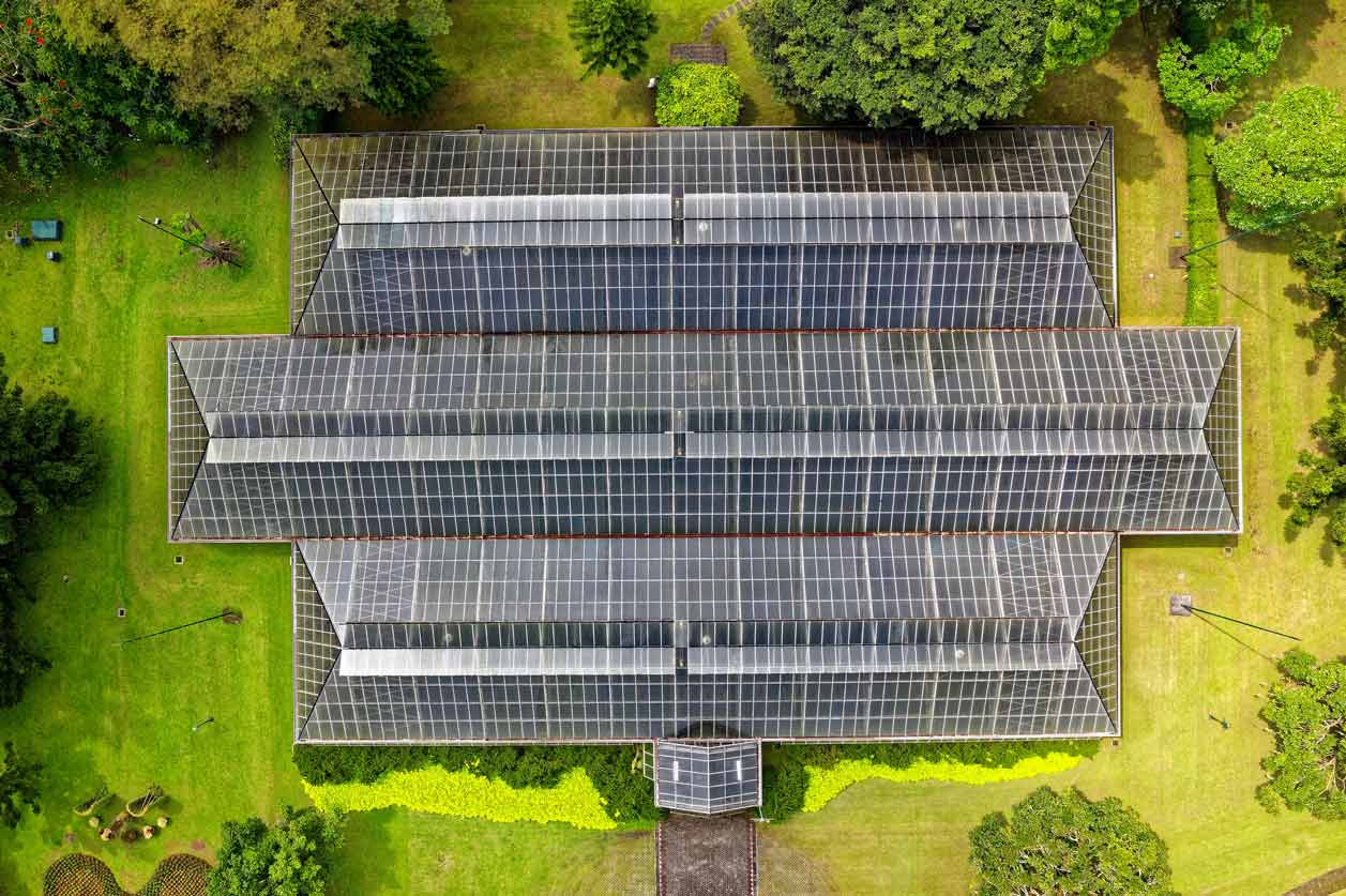 Aerial View of Solar Panel Roof. Building is surrounded by green grass and trees.