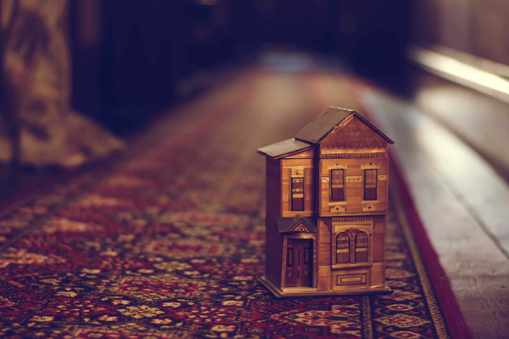 A close-up of a small model of a wood-framed town house sitting on a red patterned carpet on top of wooden floor boards.
