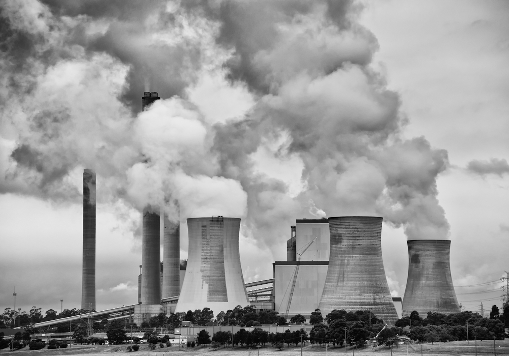 Black and white photograph, coal power station with smoke coming from large chimneys