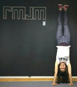 Brunette woman doing handstand against wall with chalk letters drawn on it.